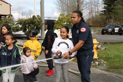 fire fighter helping young person with a fire hose