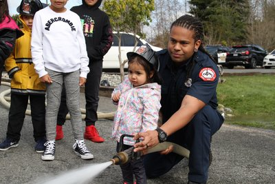 fire fighter helping little person with a fire hose
