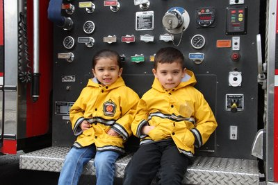kids on the back of fire engine in yellow slickers