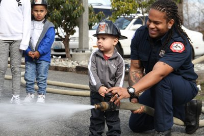 smiling fire fighter helping kid with a fire hose