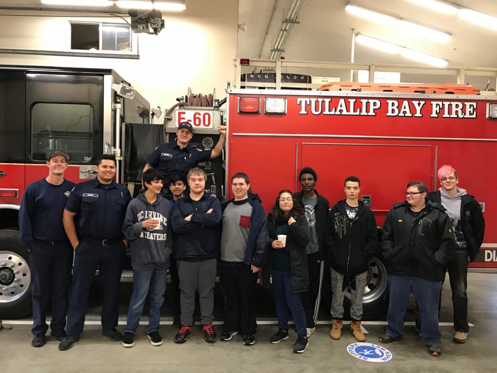 community members touring station posed in front of fire engine