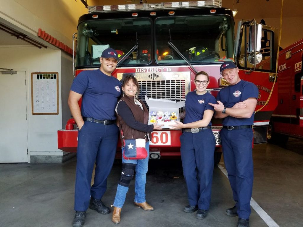 fire fighters and community member in front of fire engine during station tour