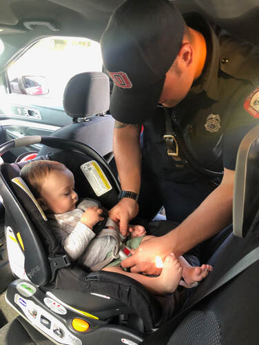fire fighter checking baby in car seat