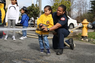 fire fighter helping child with a fire hose